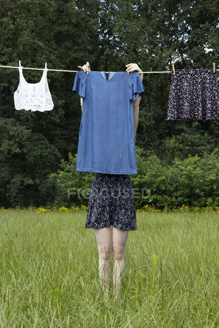 Jovem mulher se escondendo atrás do vestido de secagem no varal — Fotografia de Stock