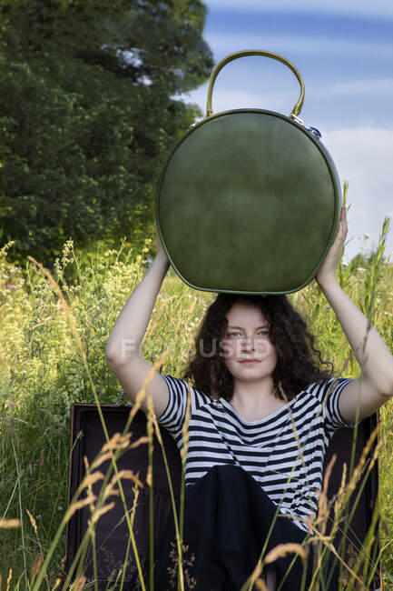 Portrait of young woman sitting in suitcase on a meadow with hatbox on top of her head — Stock Photo