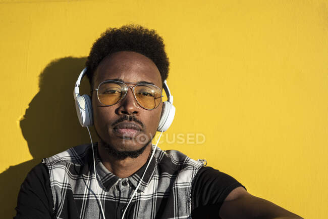 Portrait of young man listening music with headphones against yellow wall — Stock Photo
