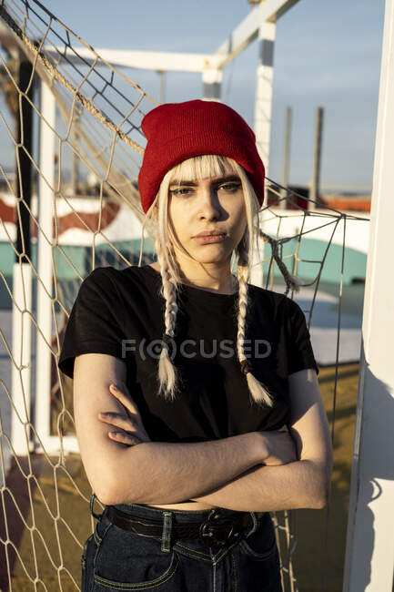 Portrait of young woman with blond braids wearing red woolly hat — Stock Photo