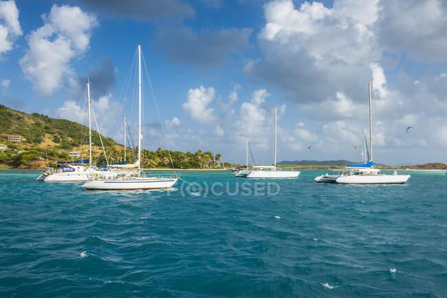 Парусник на якоре перед островом Юнион против облачного неба, Гренадины, Сент-Винсент и Гренадины, Карибский бассейн — стоковое фото