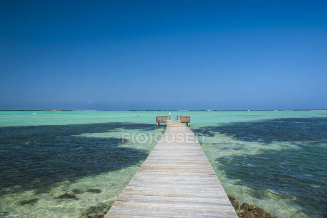 Prospettiva decrescente del molo di Lac Bay contro il cielo azzurro a Bonaire, Antille olandesi — Foto stock