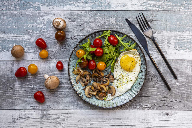Low carb breakfast with fried egg, mushrooms, rocket and tomatoes — Stock Photo