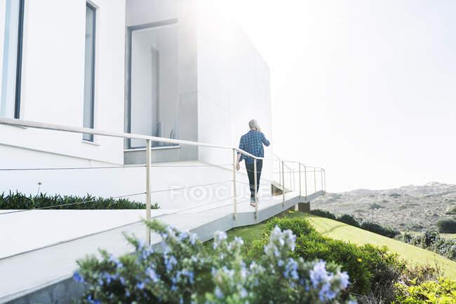 Hombre casual fuera de su casa moderna hablando por teléfono - foto de stock
