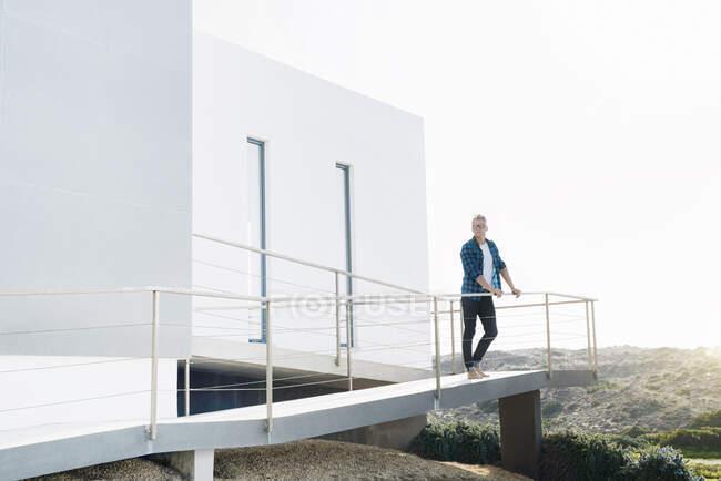 Случайный человек стоит перед своим современным домом и смотрит на пейзаж. — стоковое фото