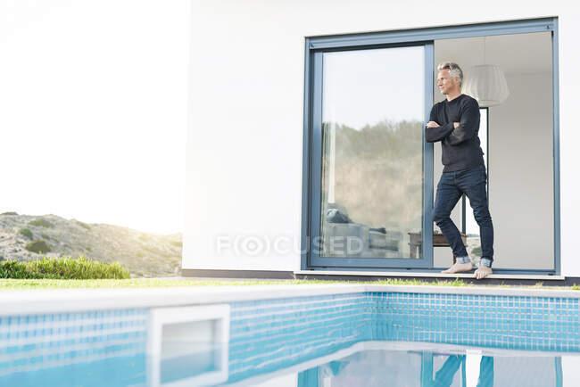Hombre inteligente de pie frente a su casa moderna con piscina mirando el paisaje - foto de stock