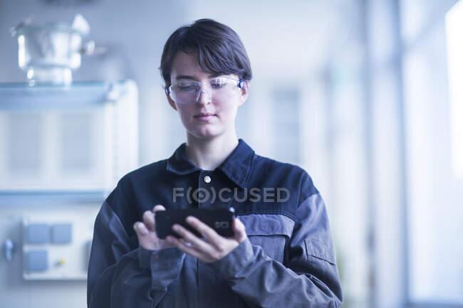 Female technician using smartphone — Stock Photo