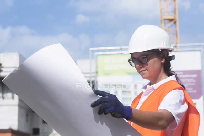 Ingeniera de construcción mirando el plan de construcción - foto de stock