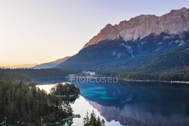 Vista panorámica del lago Eibsee con Eibsee Hotel en el fondo contra las montañas de Wetterstein, Grainau, Werdenfelser Land, Alta Baviera, Baviera, Alemania - foto de stock