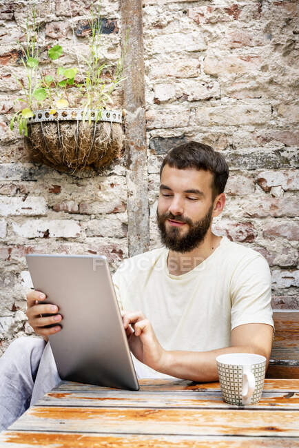 Young man sitting in backyard, using digital tablet — Stock Photo
