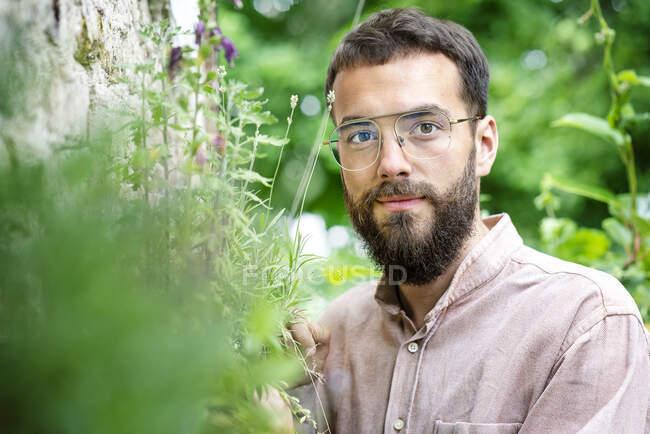 Портрет молодого бородатого человека, стоящего в саду — стоковое фото
