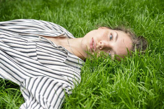 Молодая женщина лежит на траве, смотрит в камеру — стоковое фото