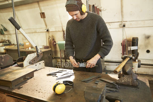 Man making knives in a workshop — Stock Photo