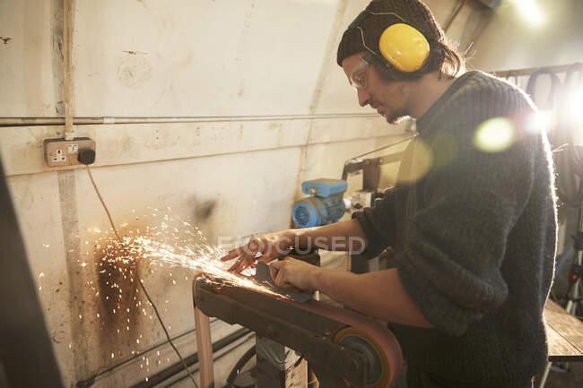 Homem moendo uma lâmina em uma oficina — Fotografia de Stock