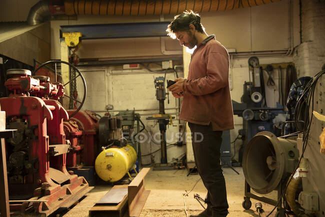 Metal worker working in workshop, using smartphone — Fotografia de Stock