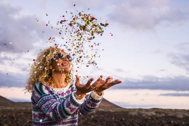 Felice donna bionda lanciando coriandoli in aria, Tenerife, Spagna — Foto stock