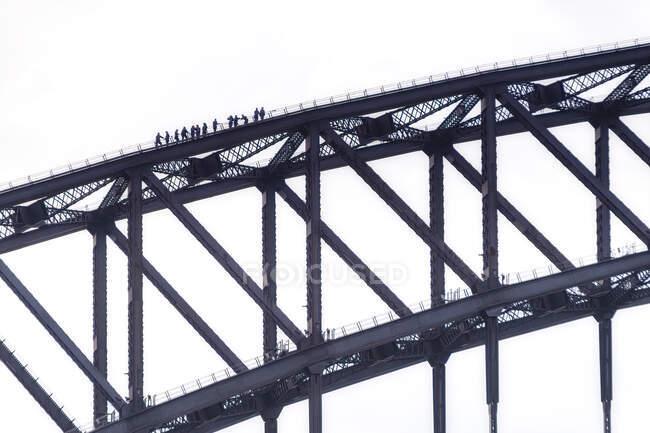 Gente de silueta escalando el puente de Sydney contra el cielo despejado, Australia - foto de stock