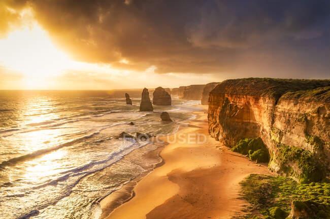 Живописный вид моря на фоне облачного неба в морском национальном парке Twelve Apostles во время заката, Виктория, Австралия — стоковое фото