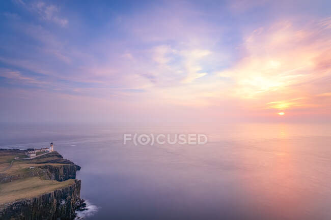 Neist Point Lighthouse by sea against cloudy sky during sunset at Waterstein, Isle of Skye, Highlands, Scotland, UK — Stock Photo