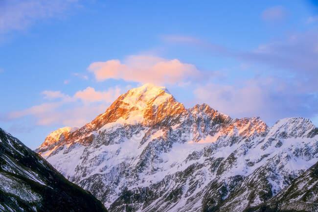 Nueva Zelanda, Isla Sur, Puesta de sol iluminando el pico nevado del Monte Cook - foto de stock