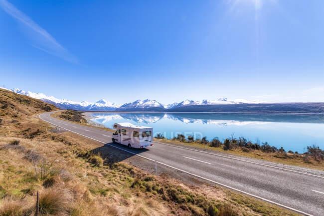 New Zealand, South Island, Motor home driving along highway surrounding Lake Pukaki — Stock Photo