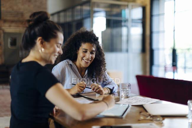 Двоє молодих бізнесменів, які працюють разом за столом на конференції в лофті. — стокове фото