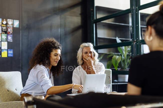 Glückliche Geschäftsfrauen mit Laptop arbeiten gemeinsam im Loft-Büro — Stockfoto