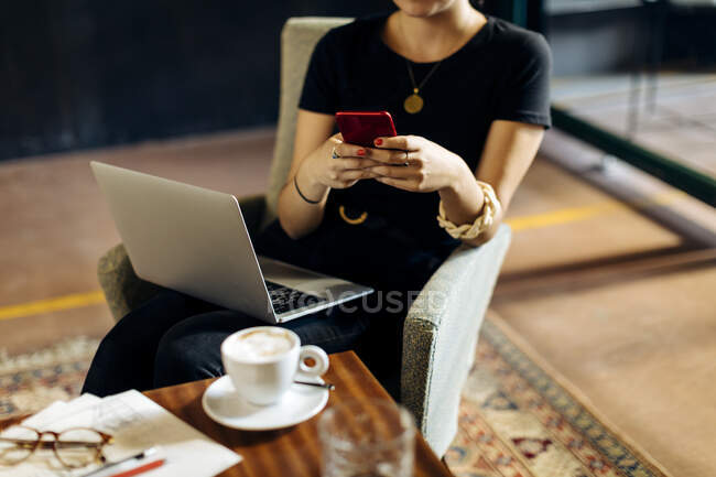 Close-up of young businesswoman with laptop and smartphone in loft office — Stock Photo