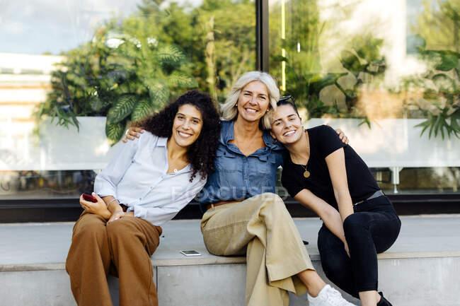 Tres mujeres sentadas en el banco de la ciudad, con los brazos alrededor - foto de stock