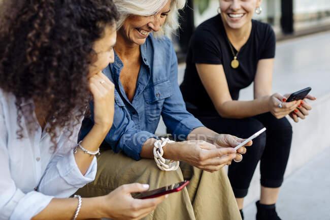 Tres mujeres sentadas en escalones seguidos, usando teléfonos inteligentes - foto de stock