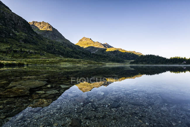 Austria, East Tyrol, Shiny lake reflecting mountains in Defereggen Valley — Stock Photo