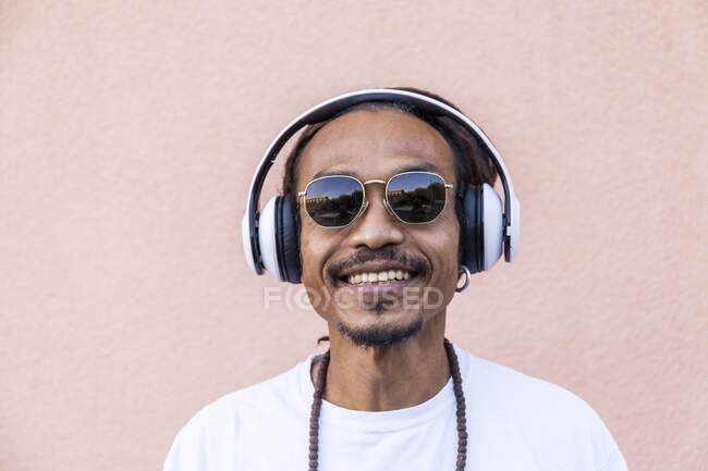 Portrait of mature man with dreadlocks and headphones, listening music — Stock Photo