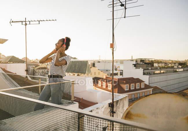 Mujer joven y feliz de pie en la azotea al atardecer escuchando música con auriculares - foto de stock
