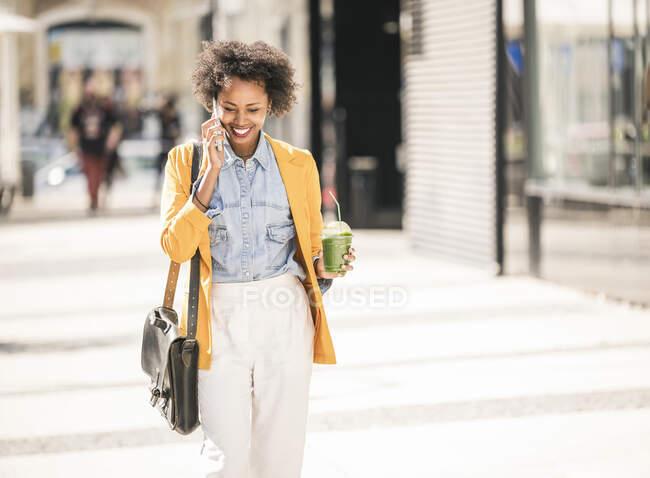 Jovem feliz ao telefone na cidade — Fotografia de Stock