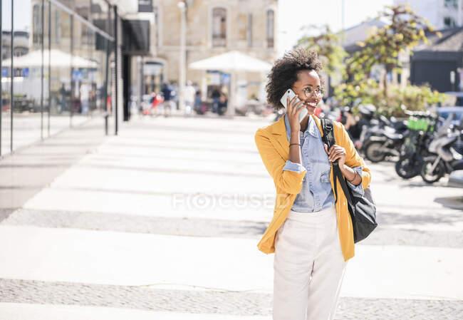 Счастливая молодая женщина по телефону в городе — стоковое фото