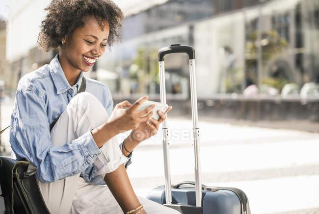 Щаслива молода жінка сидить на лавці з валізою за допомогою мобільного телефону. — стокове фото