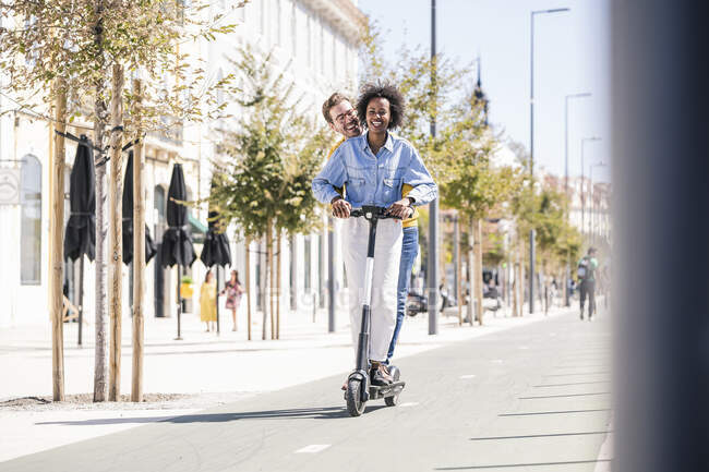 Happy young couple riding e-scooter in the city — Stock Photo