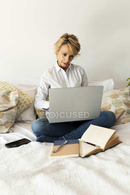 Mature woman sitting on bed at home using laptop — Stock Photo