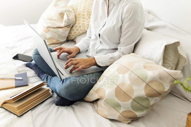 Жінки, які сидять вдома на ліжку з ноутбуком. — стокове фото