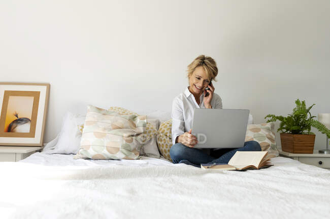 Mature woman sitting on bed at home using smartphone and laptop — Stock Photo