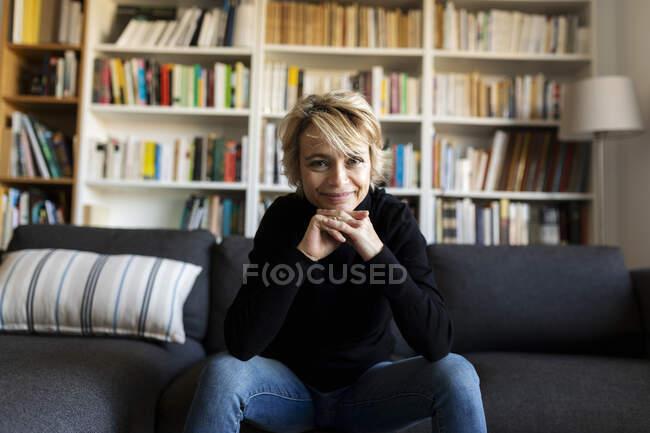 Портрет улыбающейся зрелой женщины, сидящей дома на диване — стоковое фото