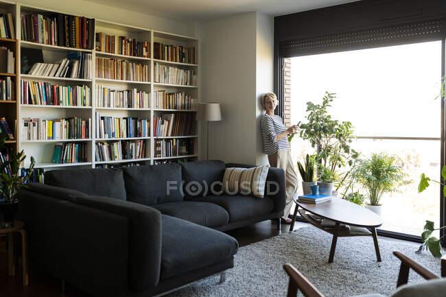 Доросла жінка стоїть біля вікна у вітальні вдома. — стокове фото
