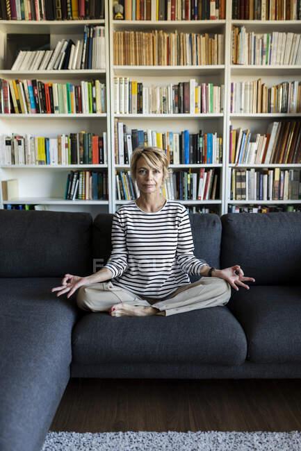 Зрелая женщина практикует йогу на диване дома — стоковое фото