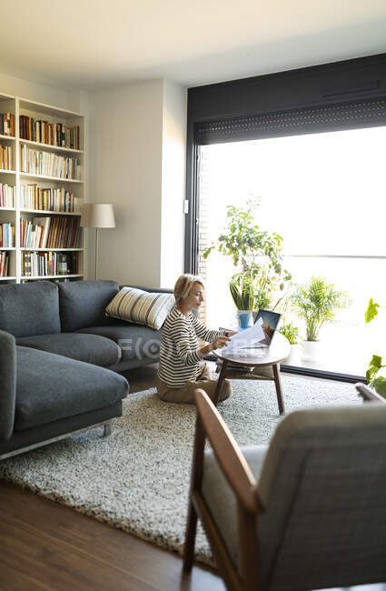 Mature woman with documents using laptop at home — Stock Photo