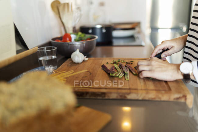 Close-up of woman cooking in kitchen at home cutting vegetables — Stock Photo