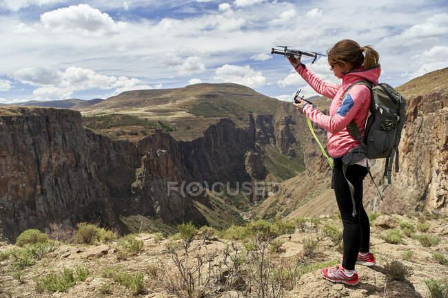 Mujer preparándose para volar un dron en las montañas, Maletsunyane Falls, Lesotho - foto de stock