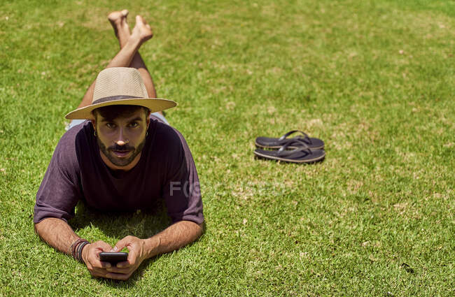 Man lying in grass using his smartphone — Stock Photo