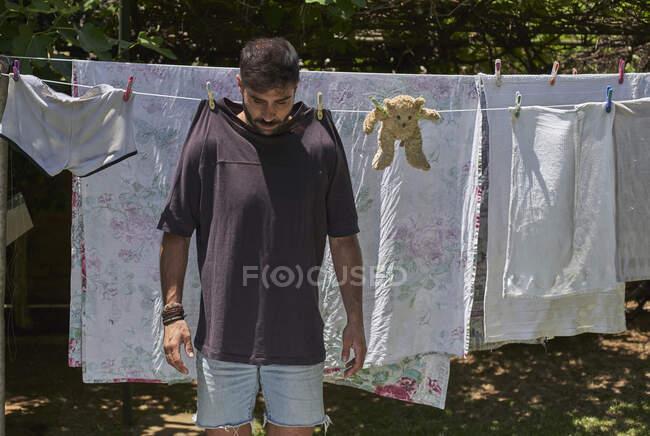 Hombre y oso de peluche colgando en un tendedero - foto de stock