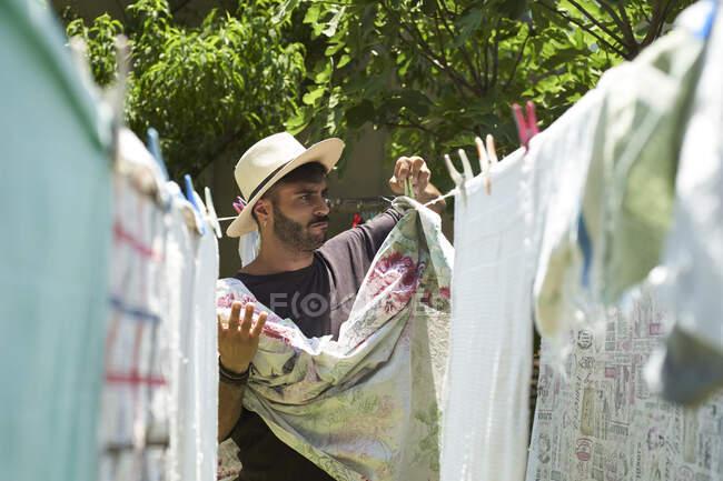 Чоловік кладе білизну на вулицю. — стокове фото