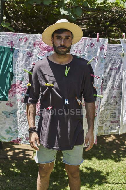 Hombre fijado con clavijas de ropa en un tendedero - foto de stock